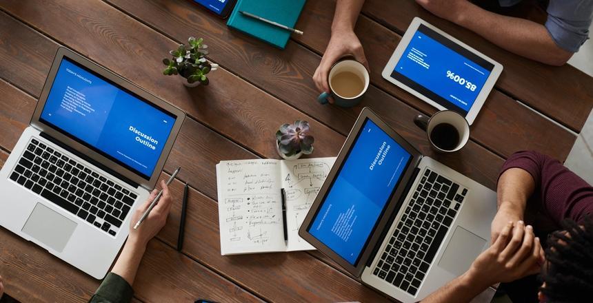 Bilde av et bord med mennesker som sitter med ulike enheter som datamskin, mobil, nettbrett osv.
