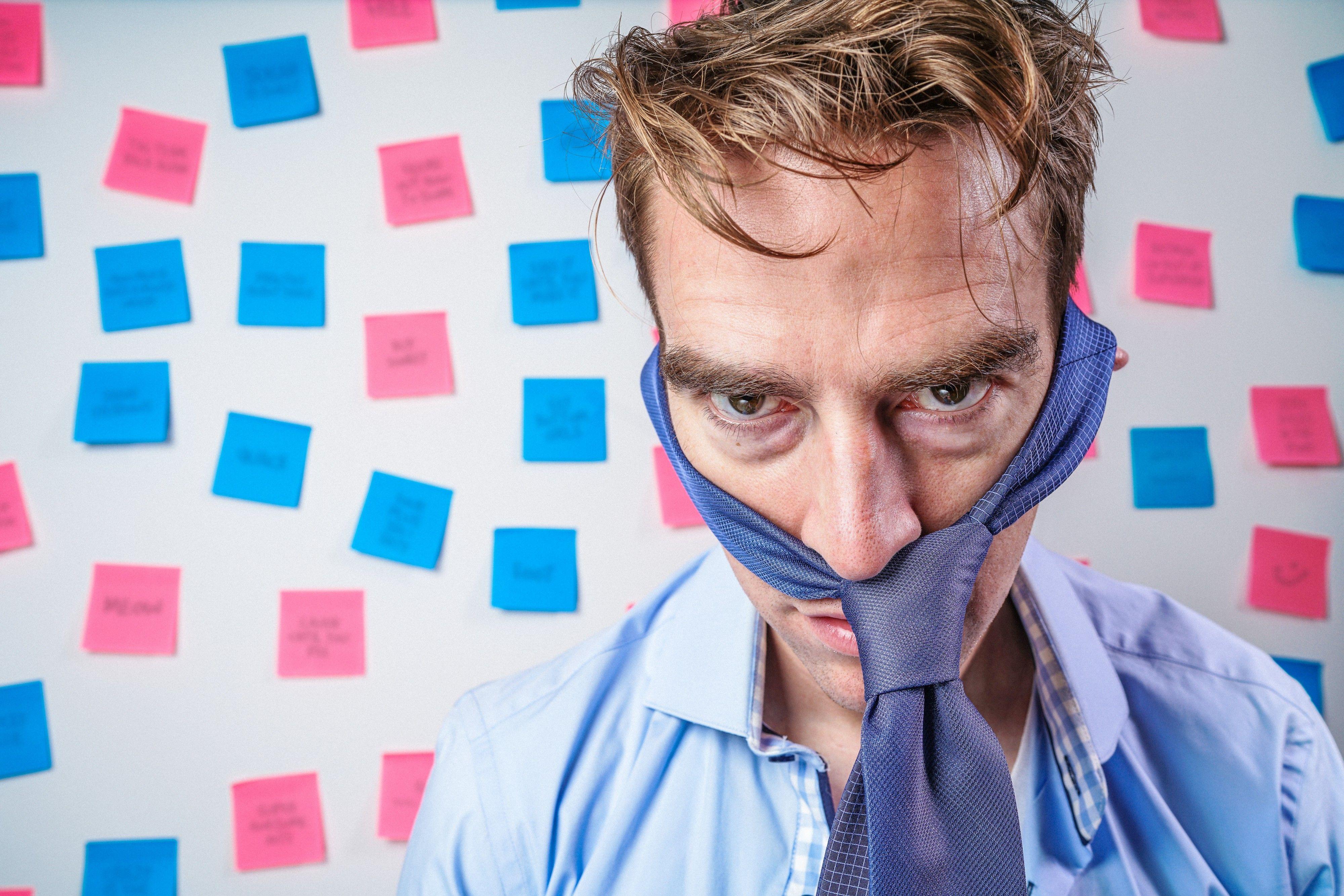 En sliten mann med slipset rundt hodet