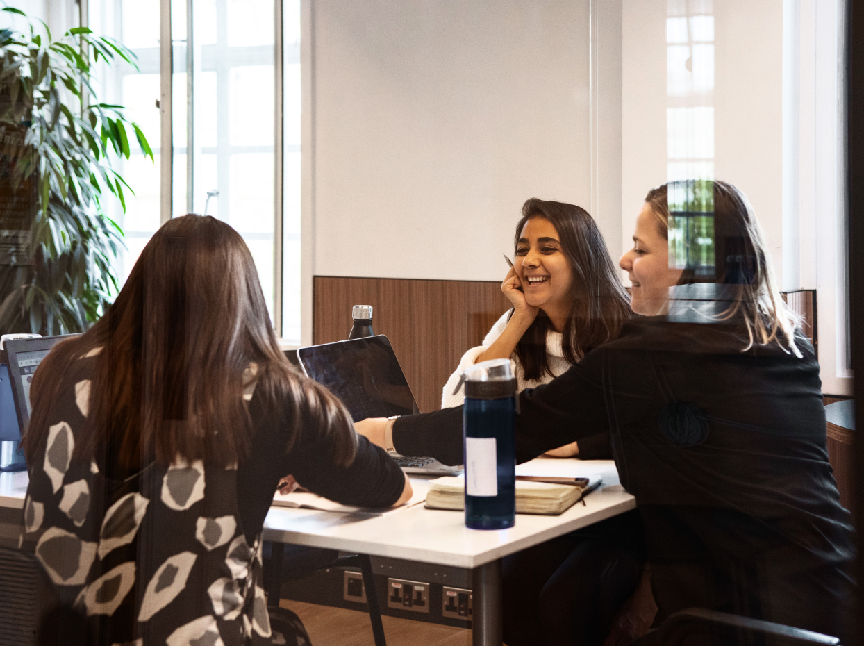 Three women in a meeting talking and smiling