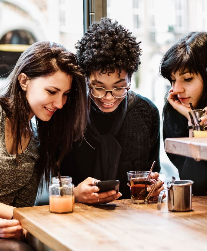 Three people smiling and looking at a phone