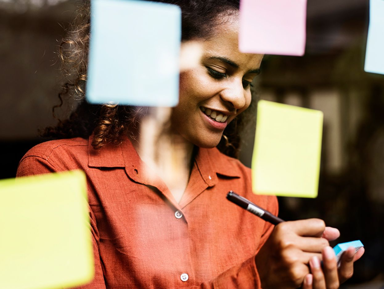 Young professional writing on a post it and smiling