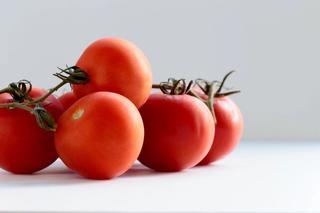Rød-oransje tomater på lys overflate
