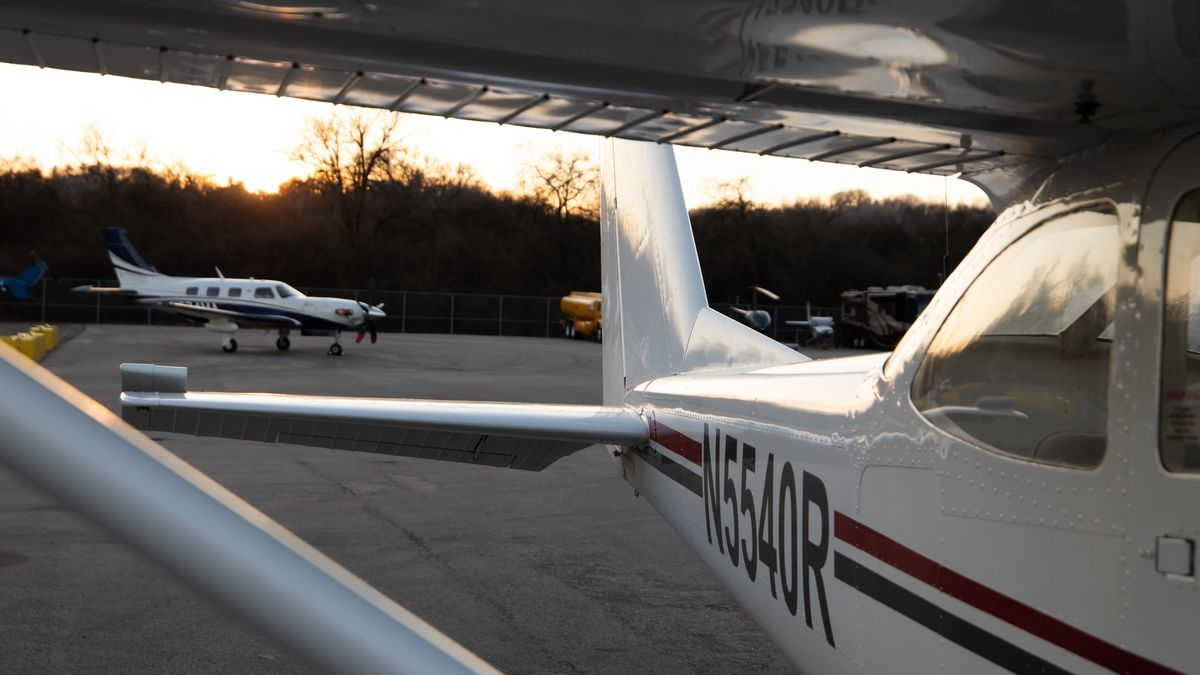 Small aircraft sitting on an airport ramp at sunset.