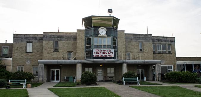 Art Deco style airport terminal and control tower with a sign reading 'Welcome to cincinnati Lunken Airport'.