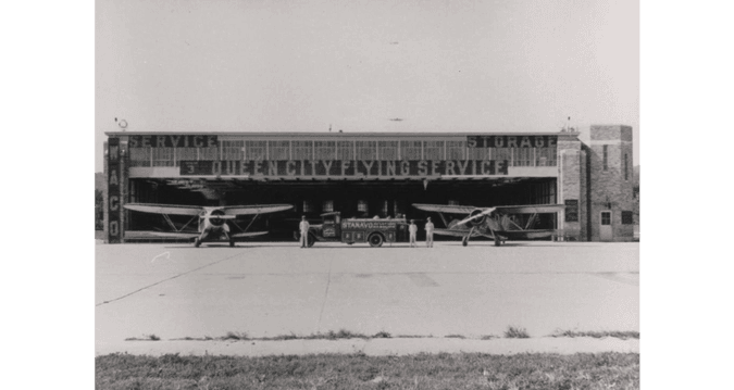 Black and white historical photo of aircraft and service equipment at Queen City Flying Service.