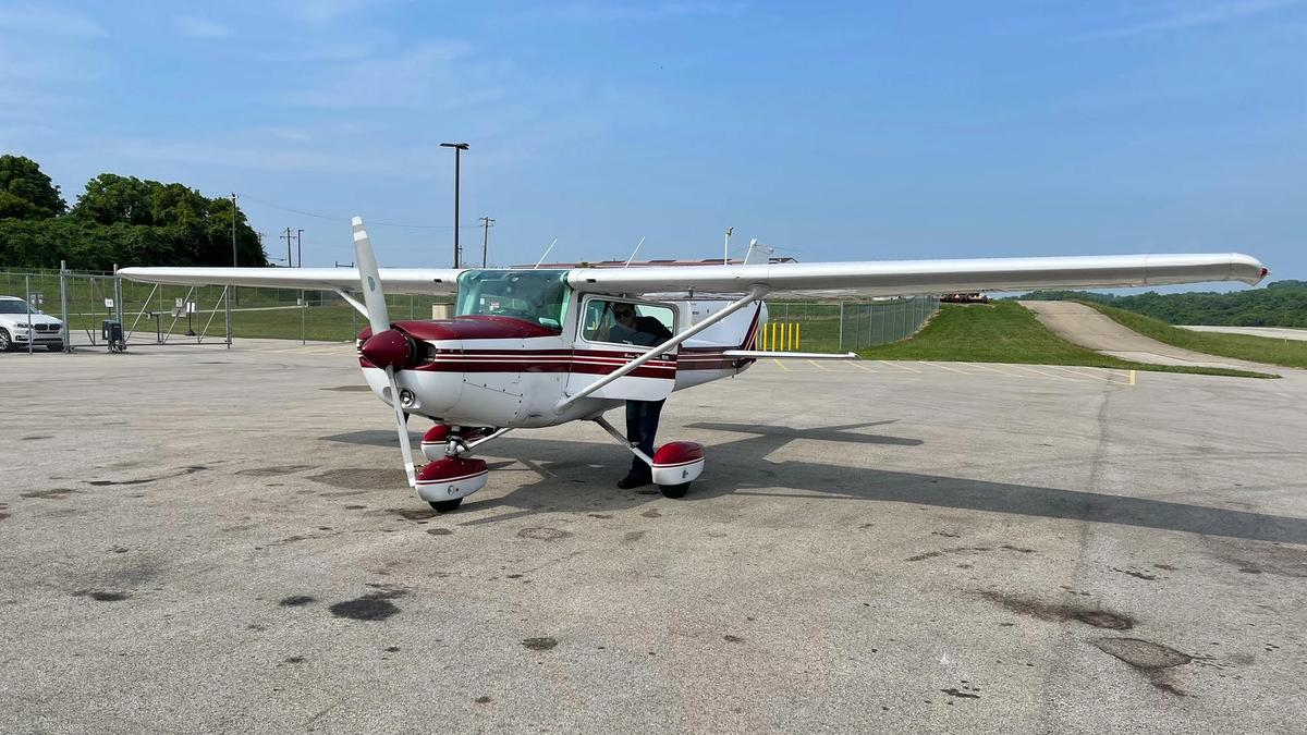 Red and white Cessna 152 parked on an airport ramp while a man waves through the window.