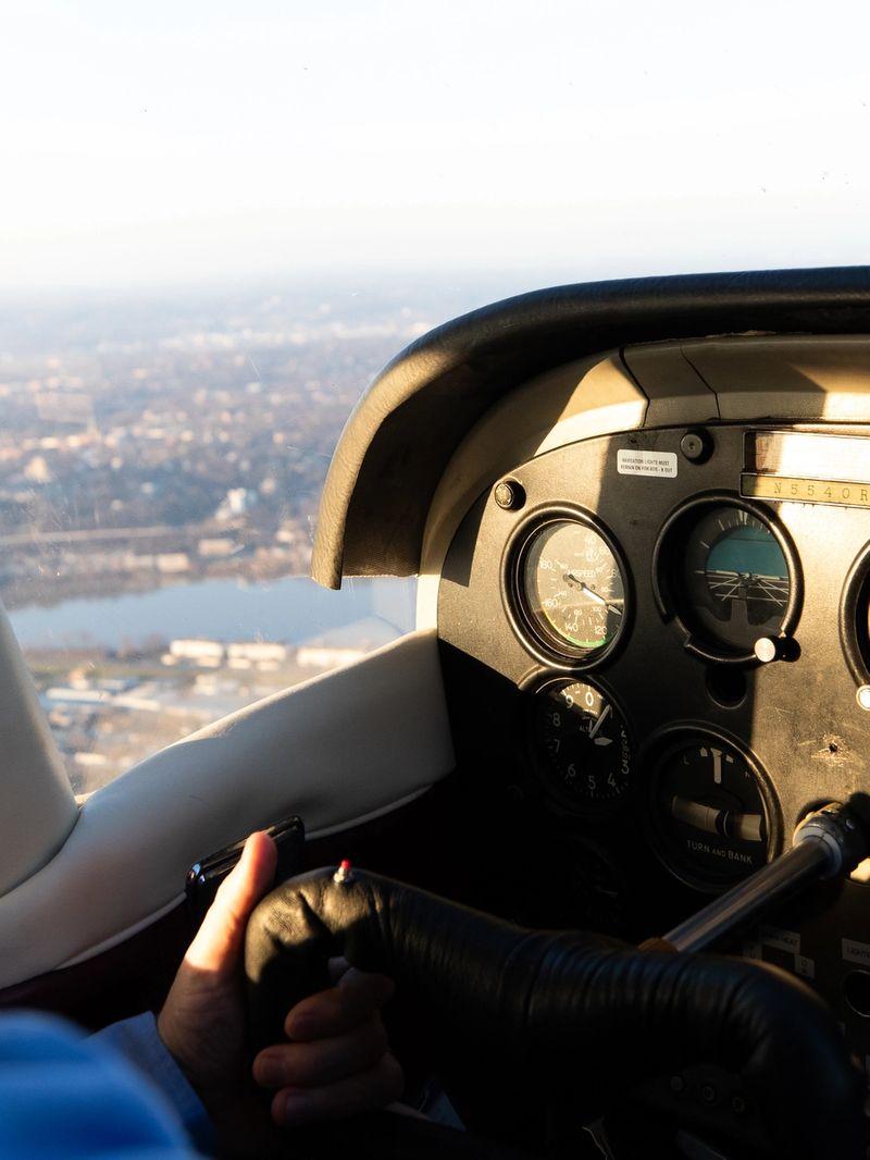 A man in a blue shirt controls a small aircraft in flight.