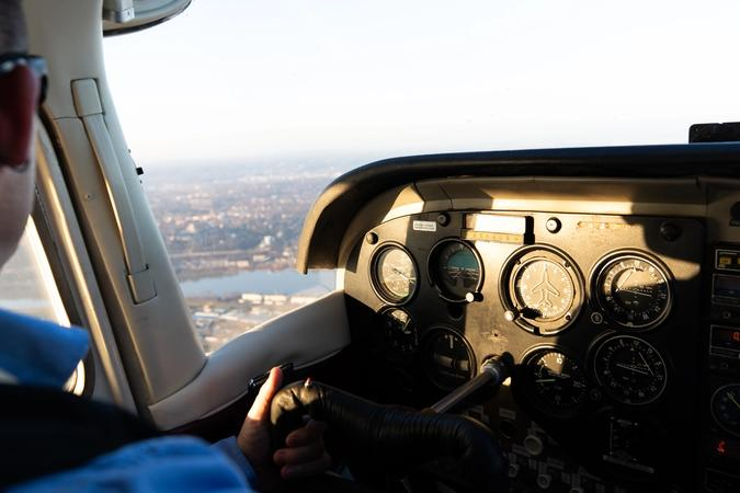 Man at the controls of a light aircraft in flight.
