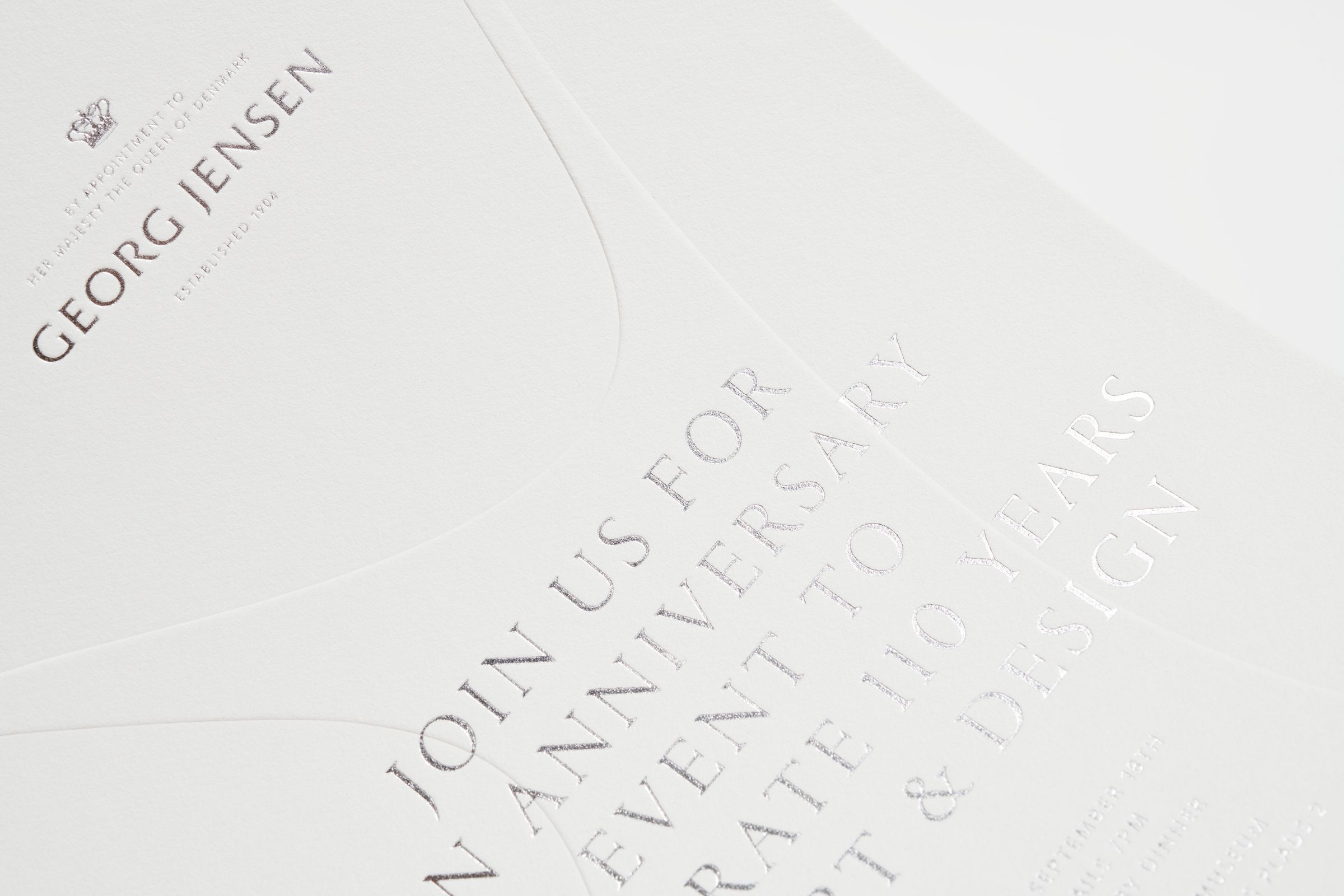 Detail of Georg Jensen invitation with silver foil and blind embossing