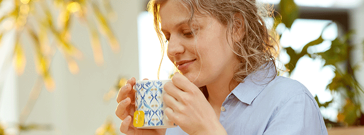 A female drinking tea in the kitchen