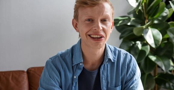 Junger Mann mit Synkinesien lächelt charmant