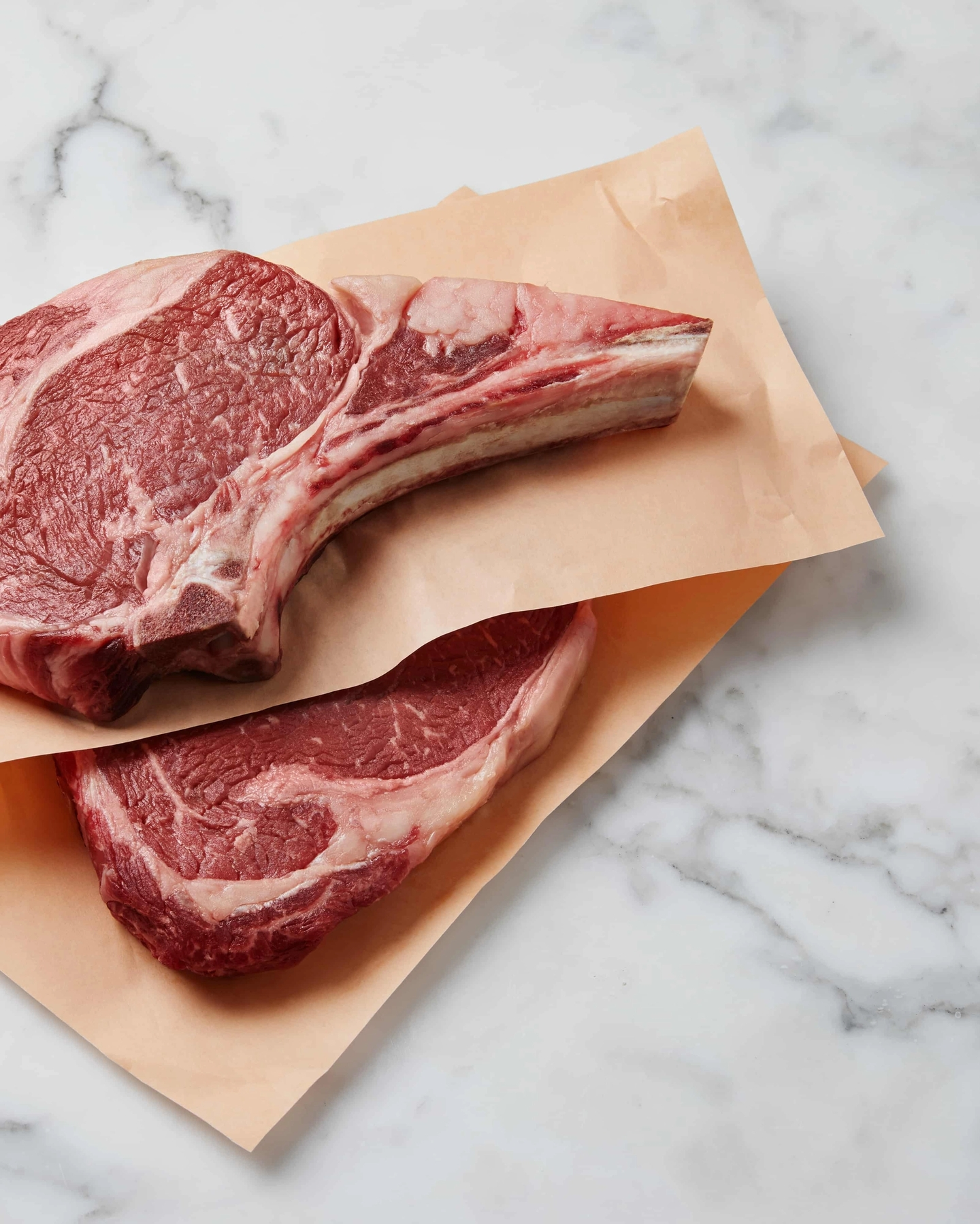 Two raw ribeye steaks on marble counter