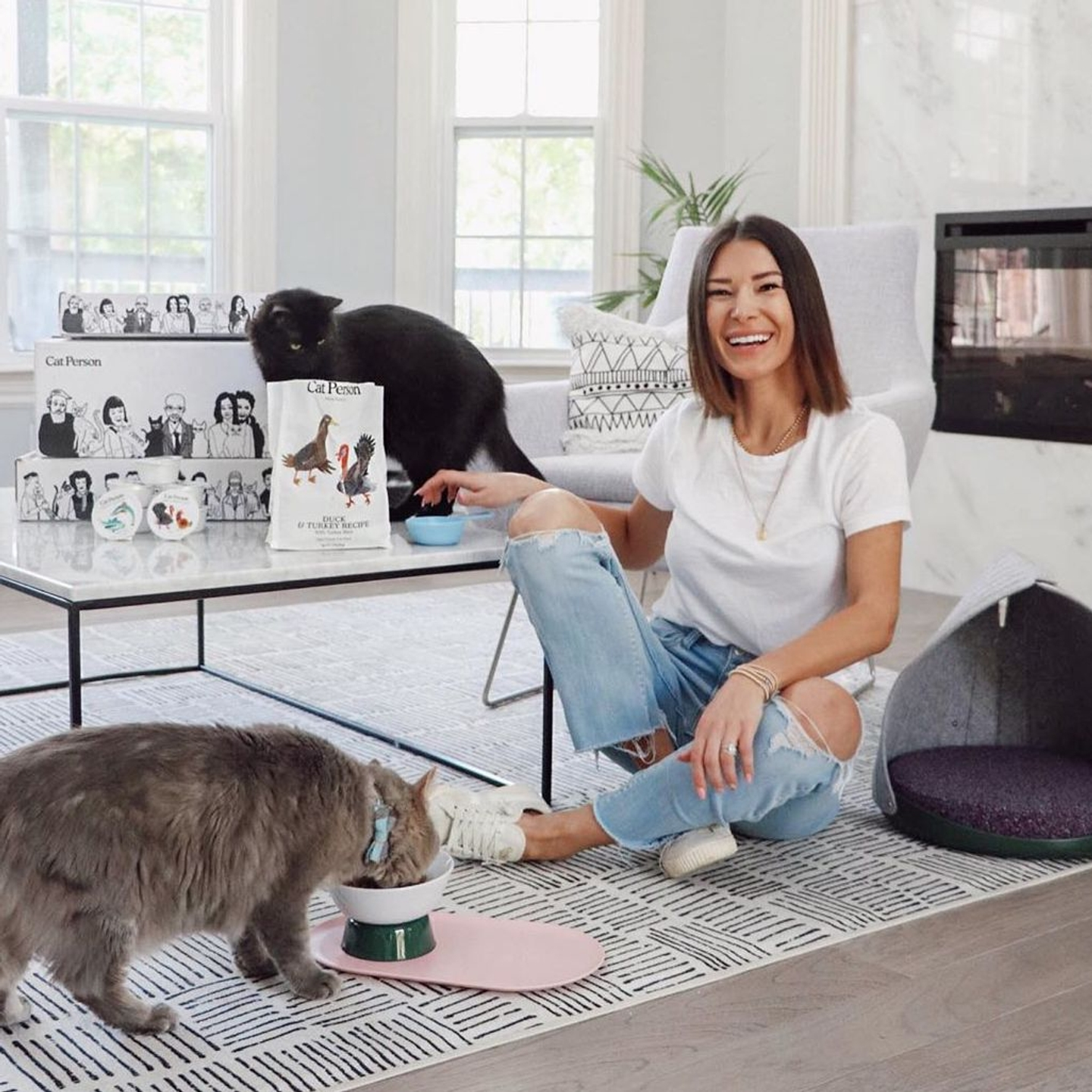 Woman smiling and sitting on floor with two cats