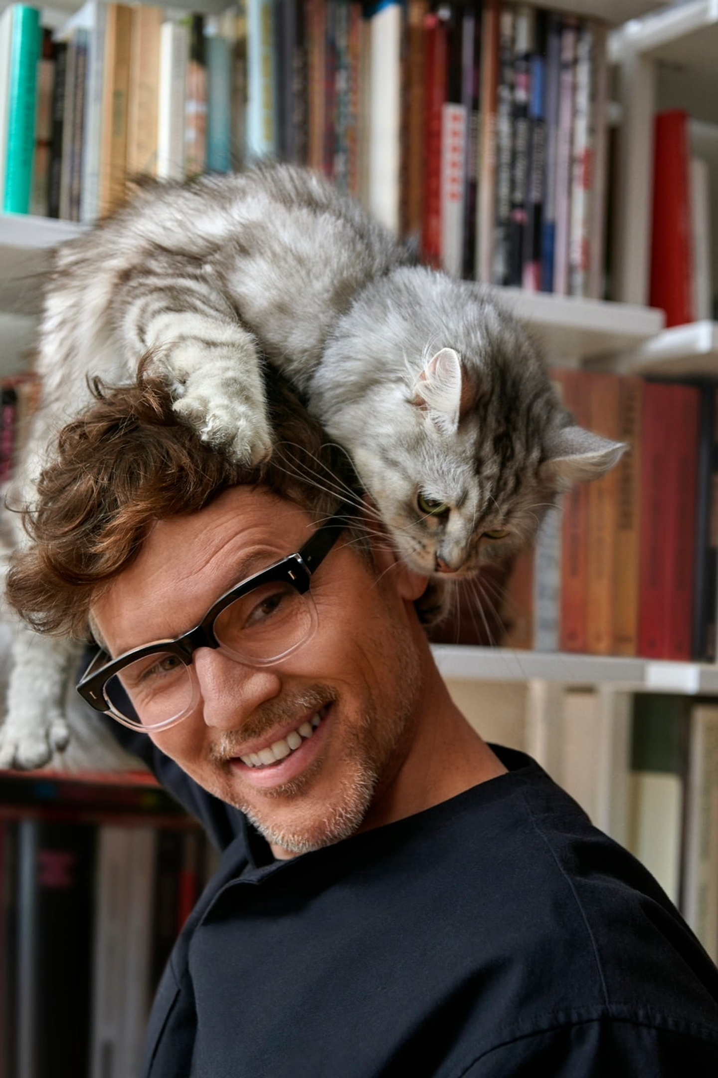 Man in glasses with cat climbing on his head
