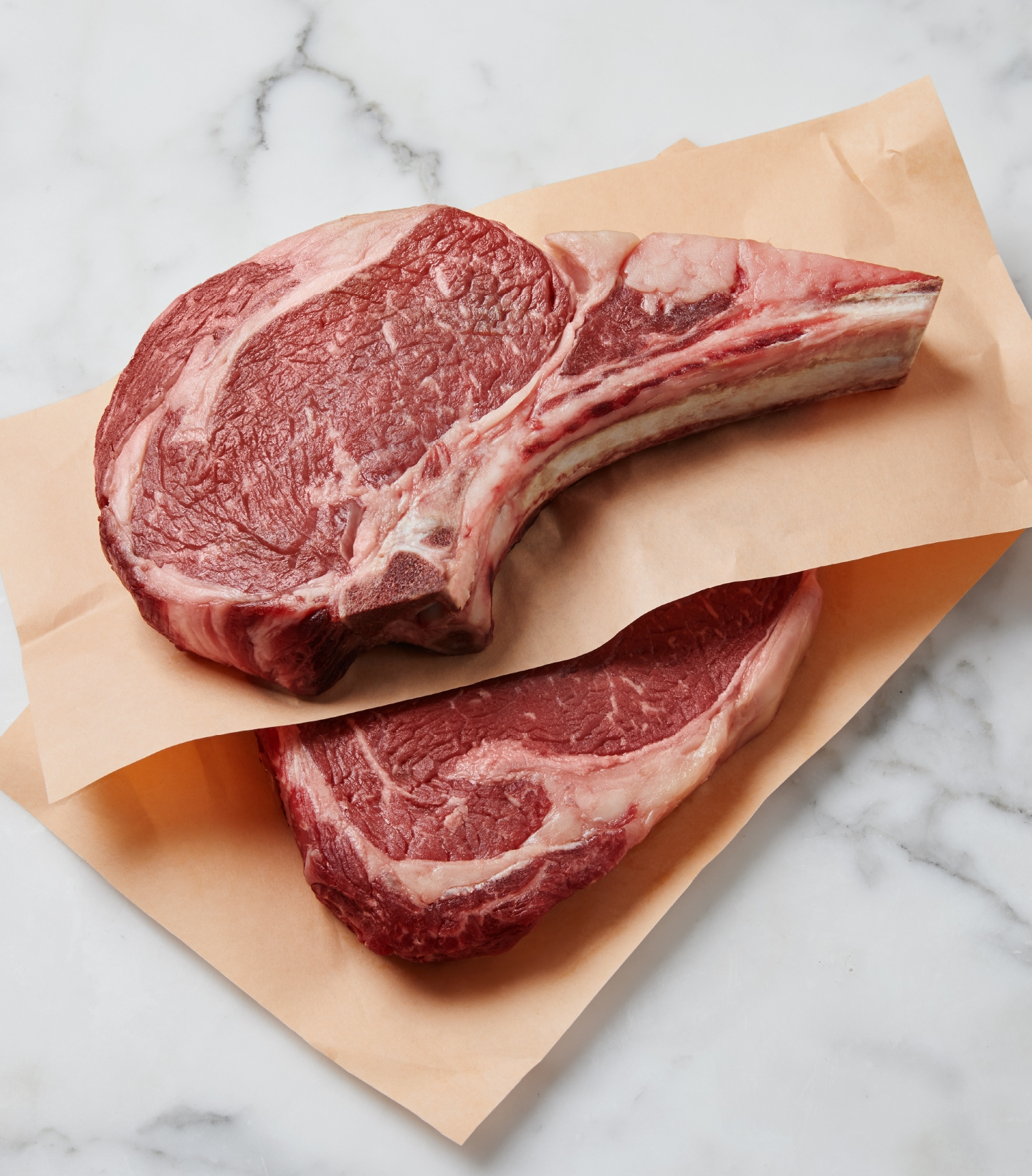 Two marbled raw beef ribeye steaks on a white marble countertop