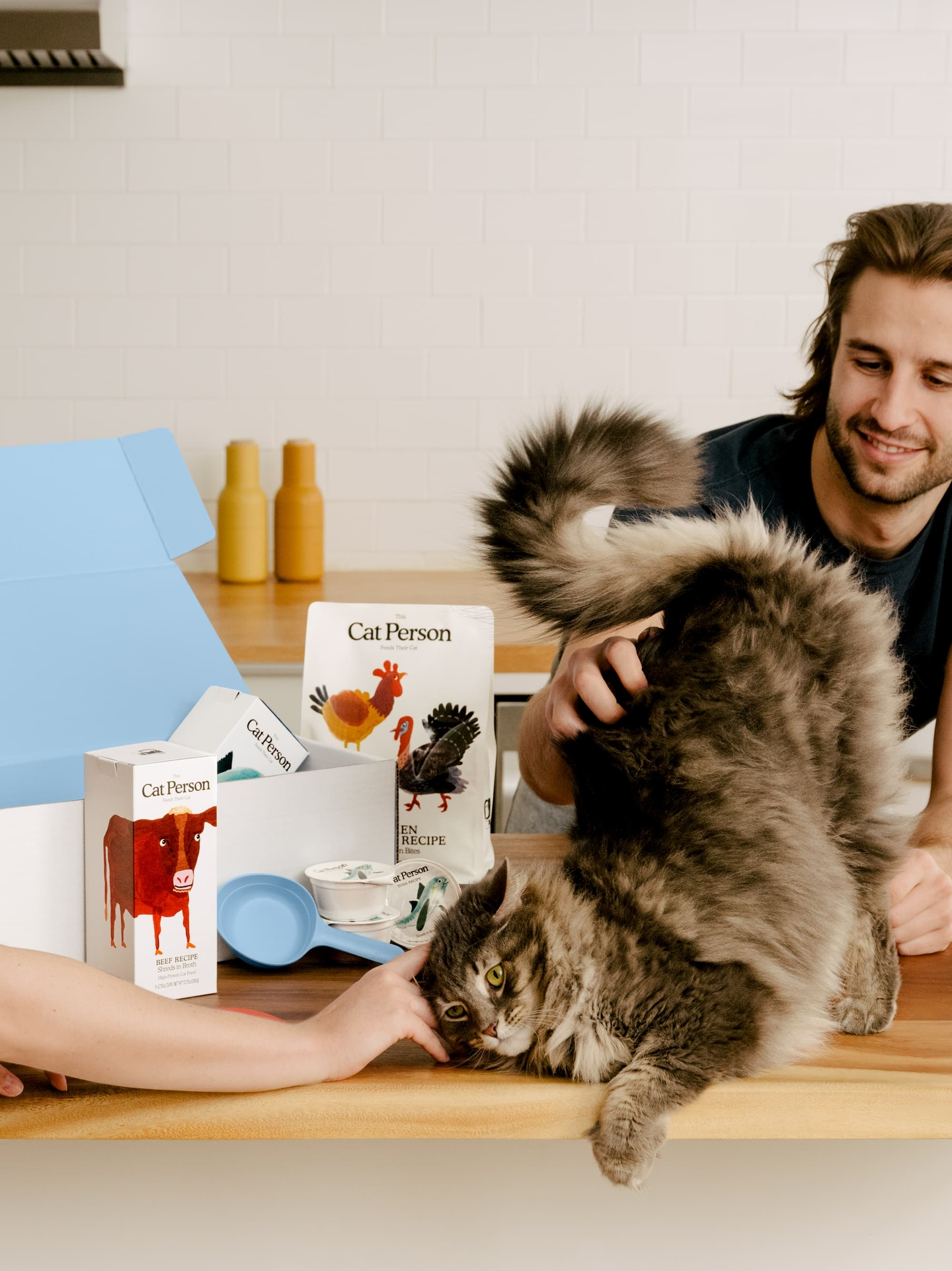 A man pets a happy cat. There is a Cat Person starter box in the background