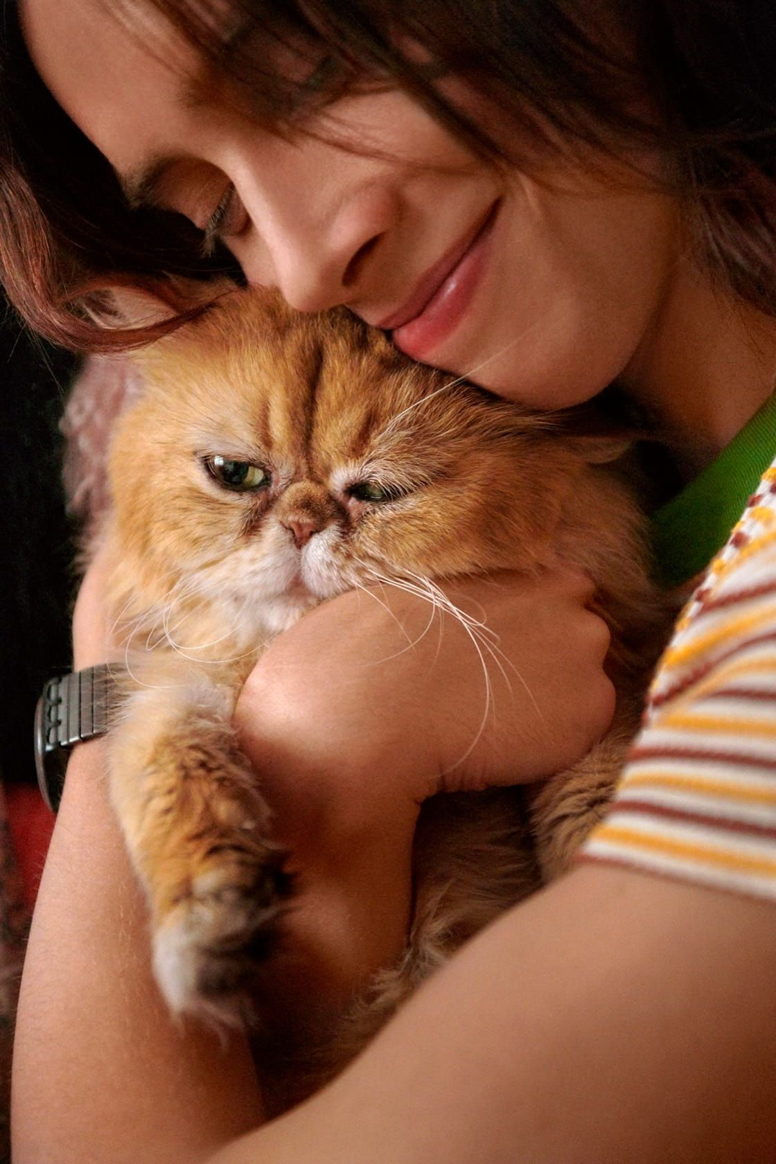 Man with long hair smiling and hugging his fluffy orange cat