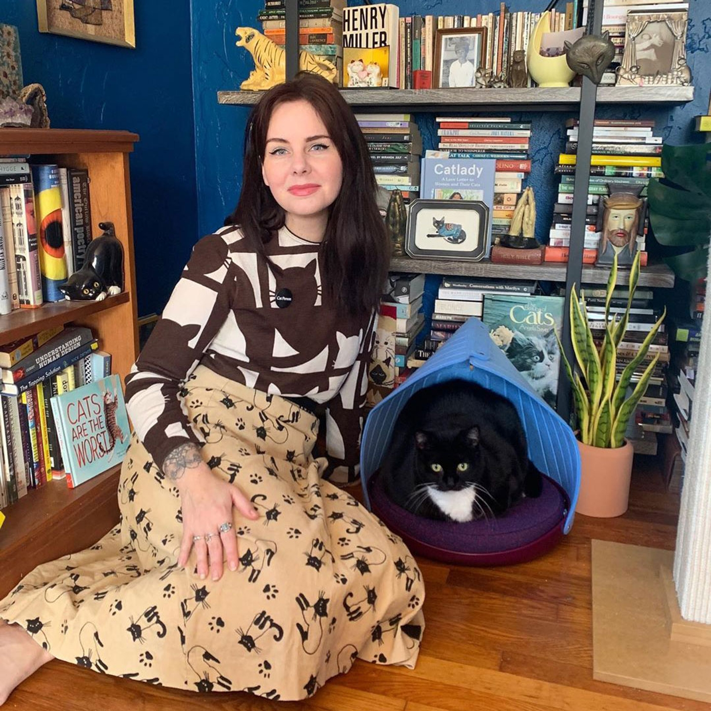 Woman sitting on wood floor next to a black cat lying in a Cat Person Canopy Bed