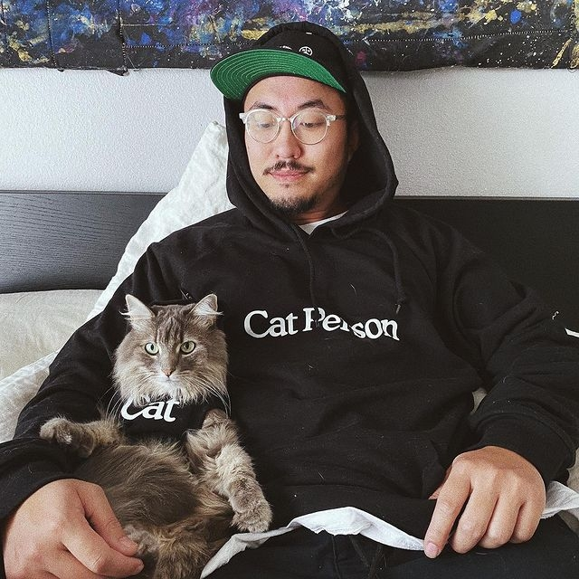 Man wearing Cat Person hoodie looking at cat wearing a cat shirt