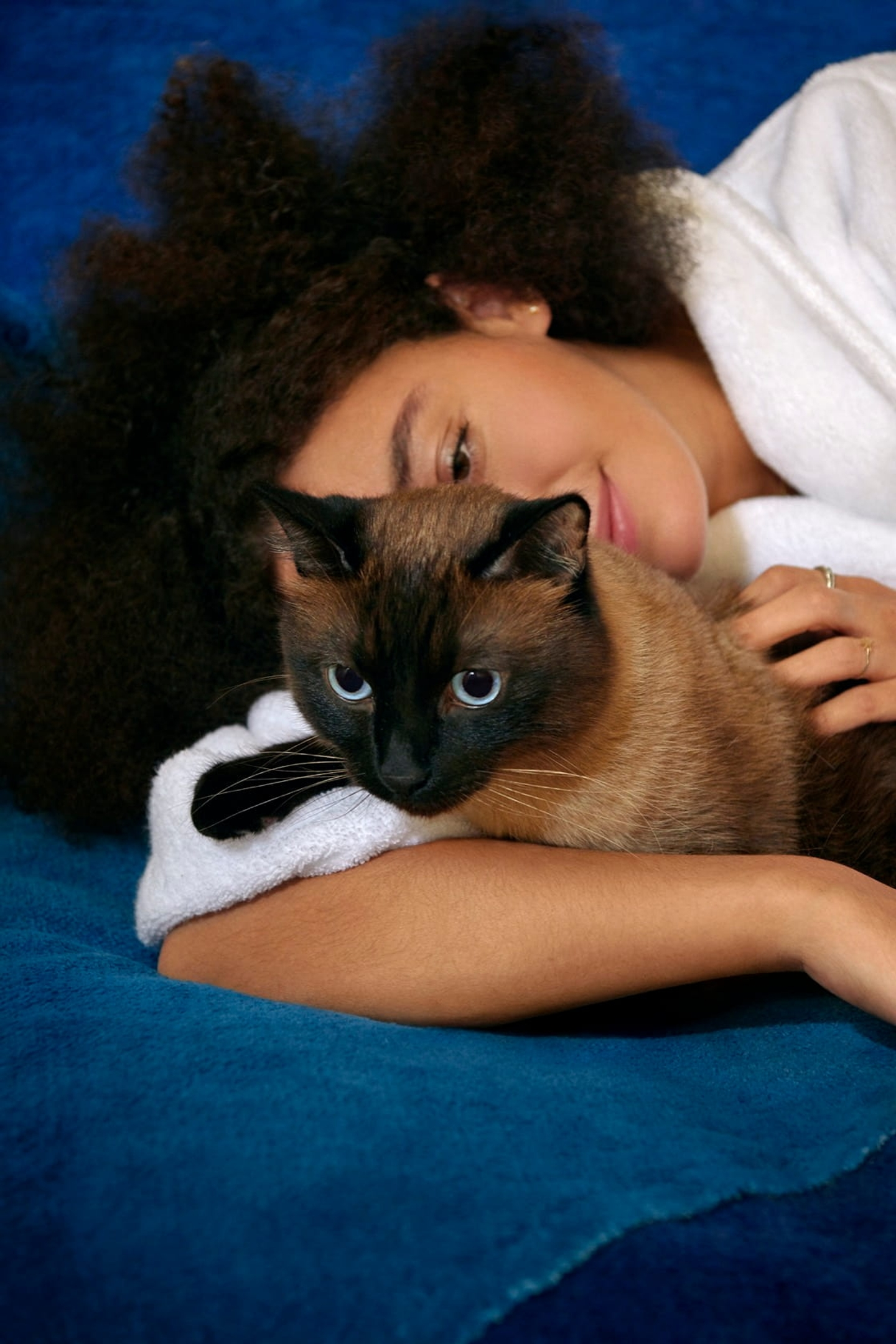 Woman in white bathrobe holding and petting her Siamese cat