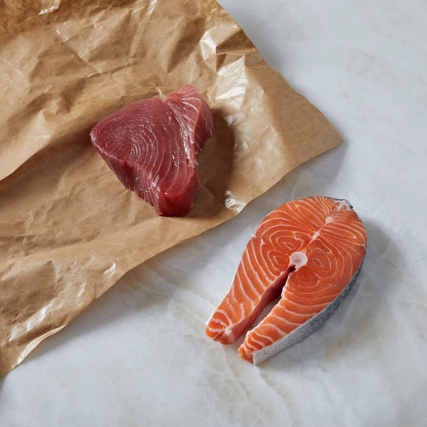 A raw piece of tuna and salmon on top of butcher paper