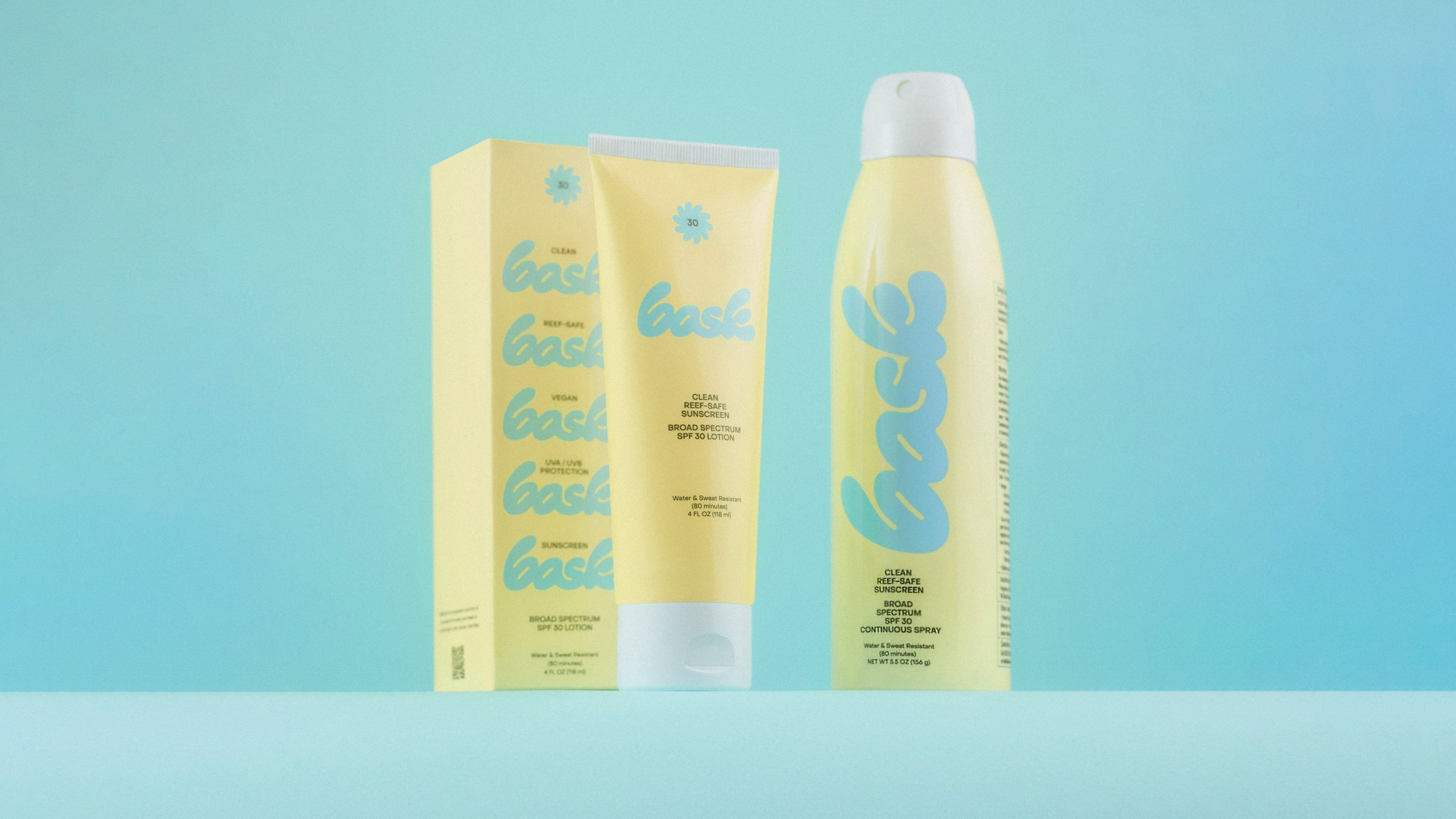Bask Sunscreen Yellow Spray Bottle and Lotion Tube on Blue Background by RoAndCo