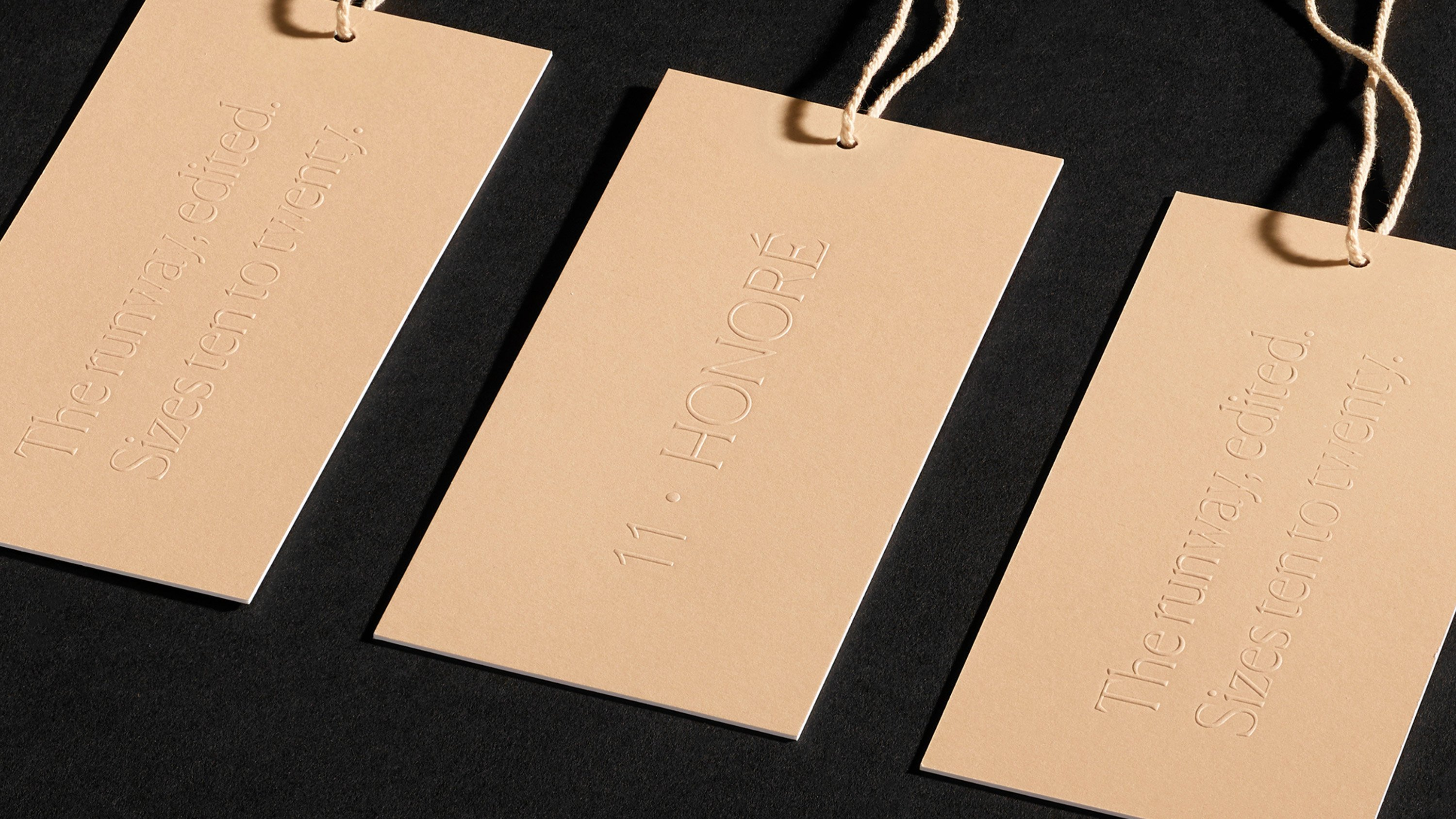 Close up of embossed 11 Honoré hang tags, print design and branding by RoAndCo