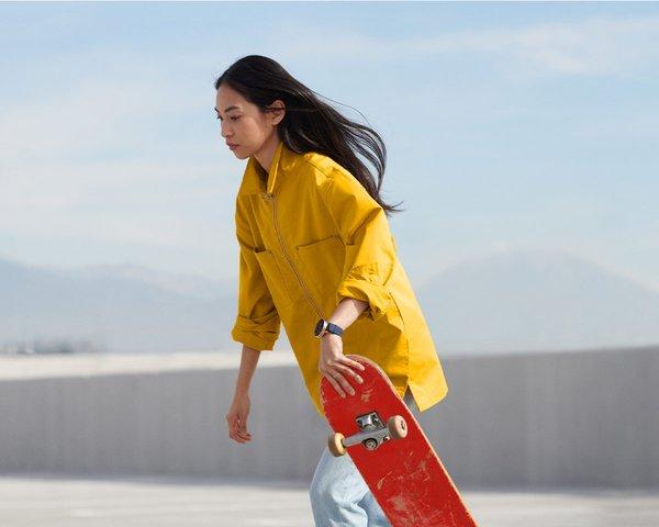 Woman skateboarding wearing a Google Wear OS watch
