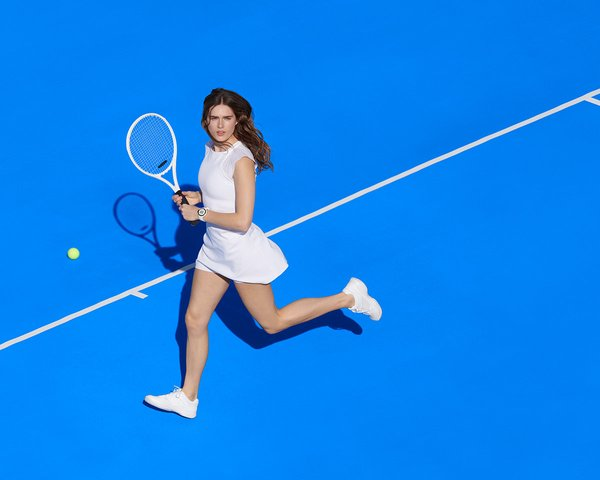 Woman playing tennis wearing a white dress and Google Wear OS watch