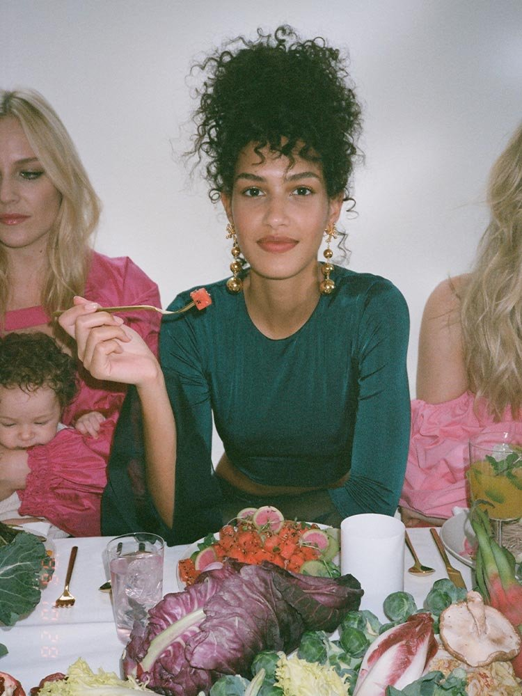Behind the scenes campaign photo, female model in green, sitting at table surrounded by fruits and vegetables. Campaign Art direction by RoAndCo