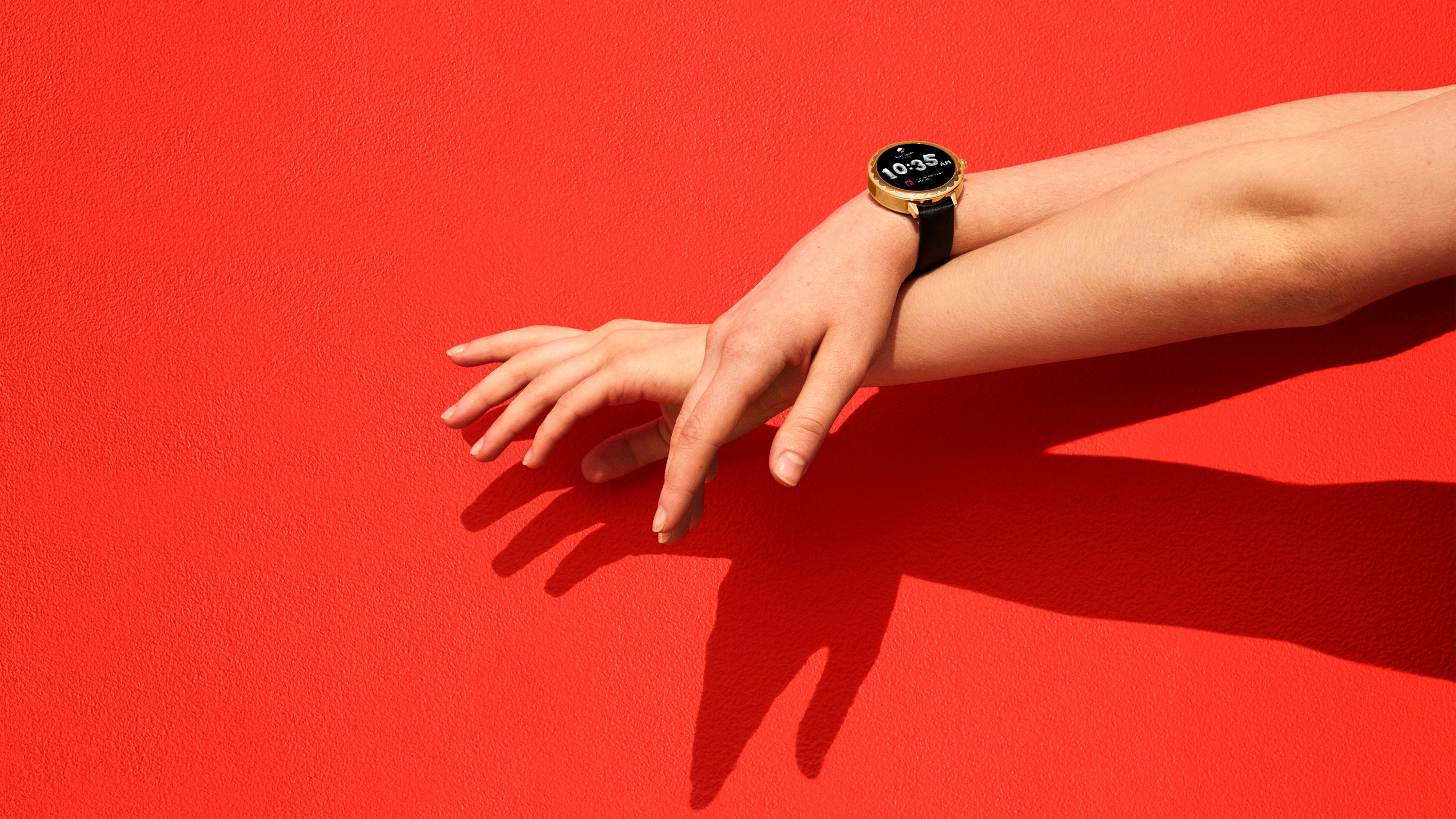 Close up of woman's arm, Wear Google OS gold watch with black band, art direction by RoAndCo