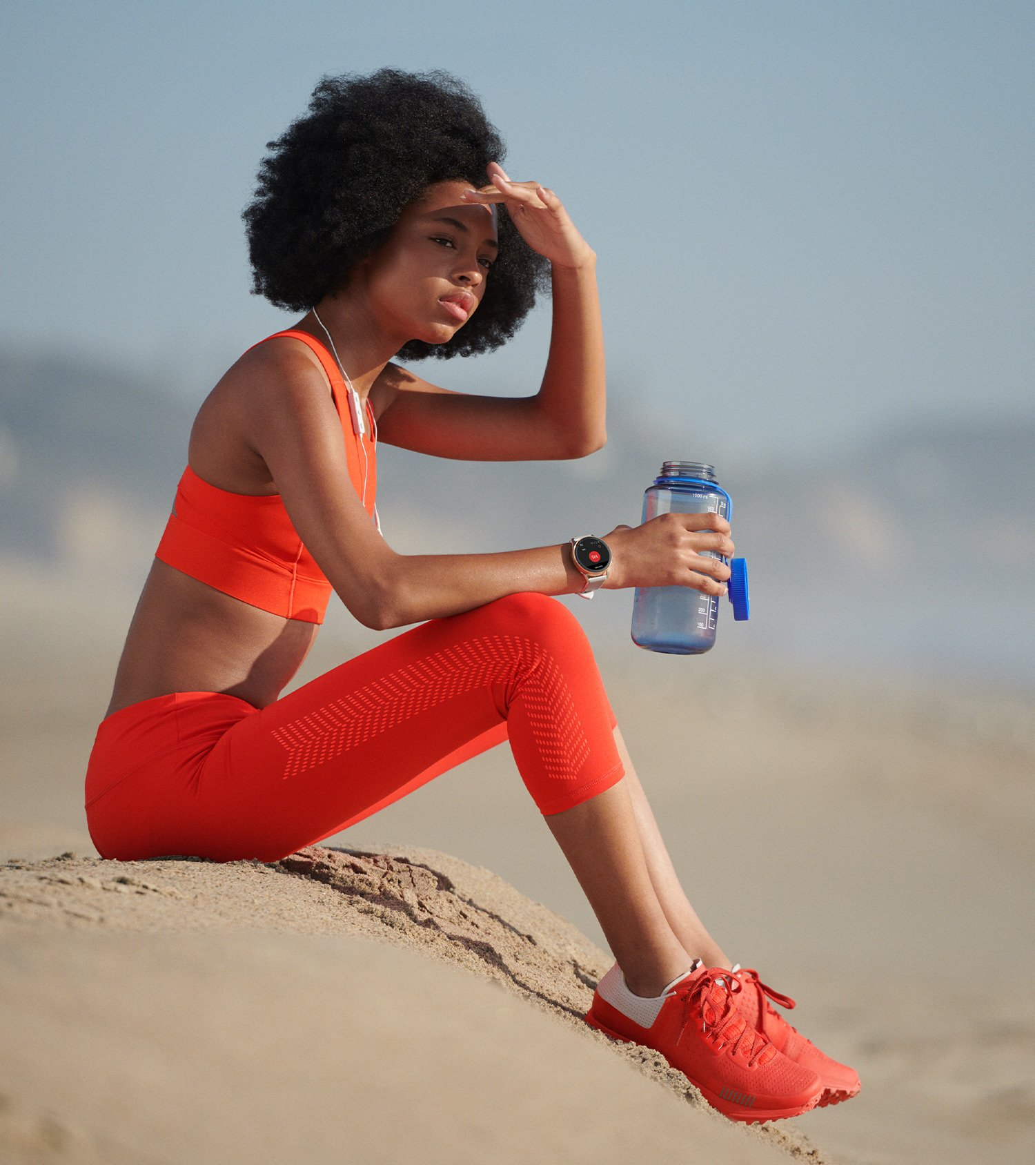 Woman sitting on the beach in all red workout attire with matching Google Wear OS watch, art direction by RoAndCo
