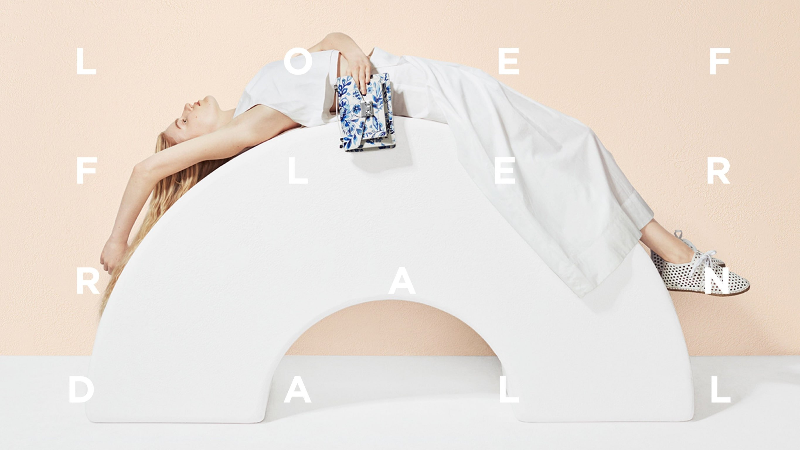Loeffler Randall ad featuring model laying on white arch wearing white sneakers and holding blue embroidered pouch. Branding and Art direction by RoAndCo