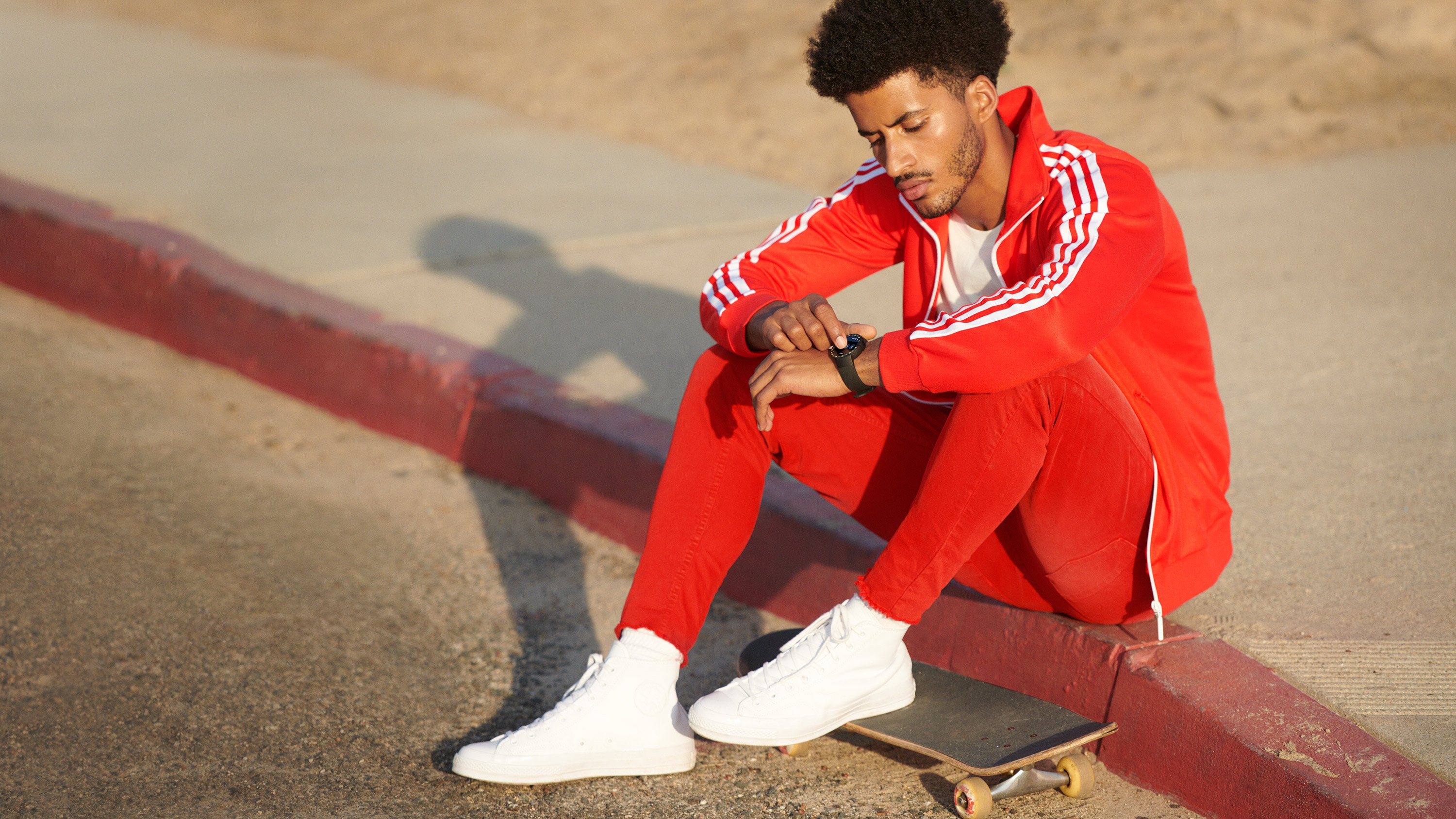 Google Wear OS lifestyle, man wearing red jumpsuit and white sneakers with matching Google Wear OS watch. Art Direction by RoAndCo