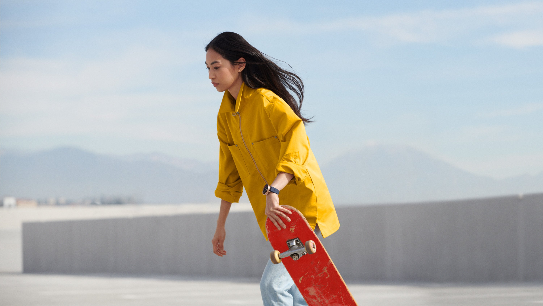 Woman in yellow jacket skateboarding, wearing black Google Wear OS watch, art direction by RoAndCo Studio