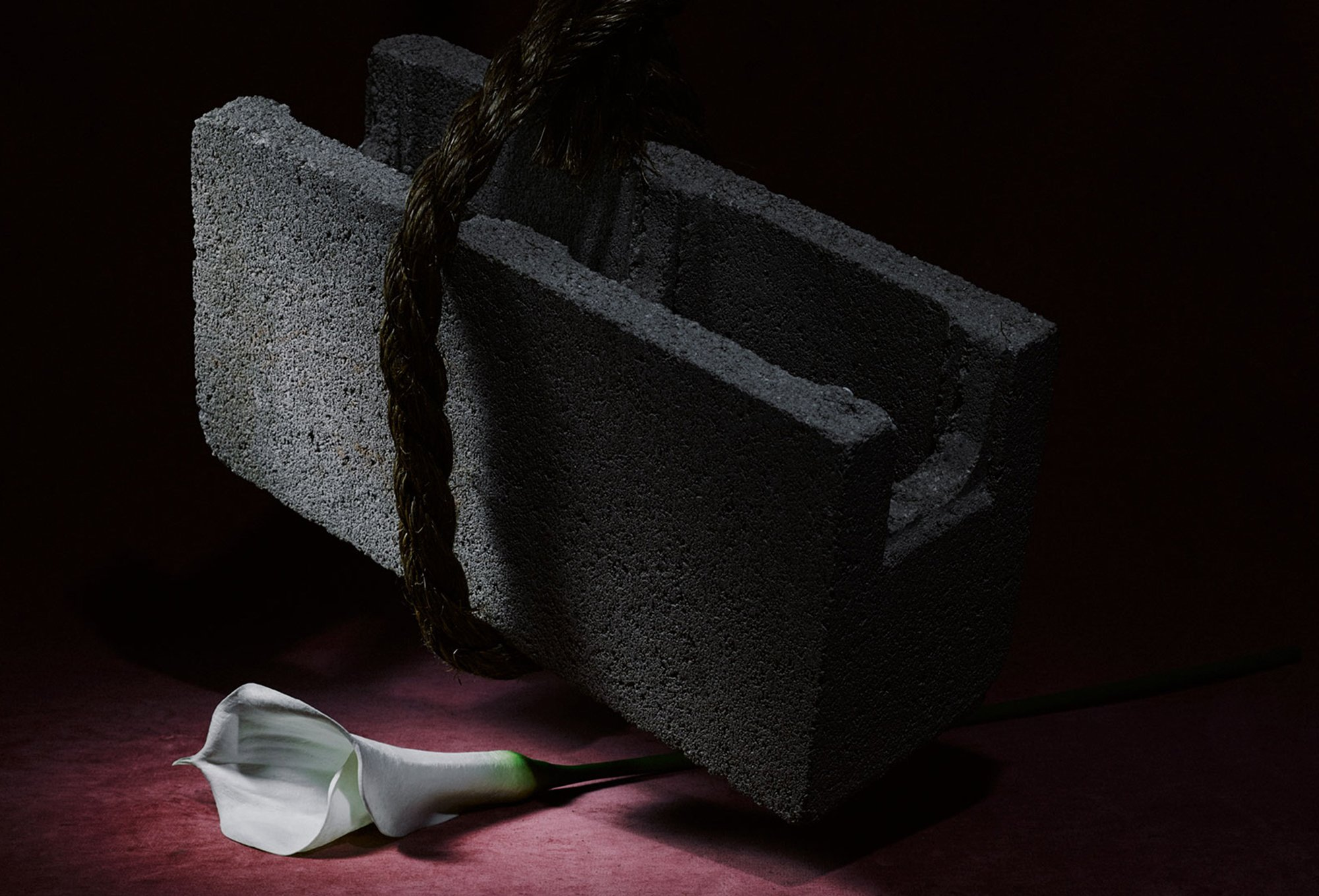 Still image of cinder block hanging over white calla lily flower for Romance Journal Issue 02 Resistance. Publication design, art direction, print design by RoAndCo.