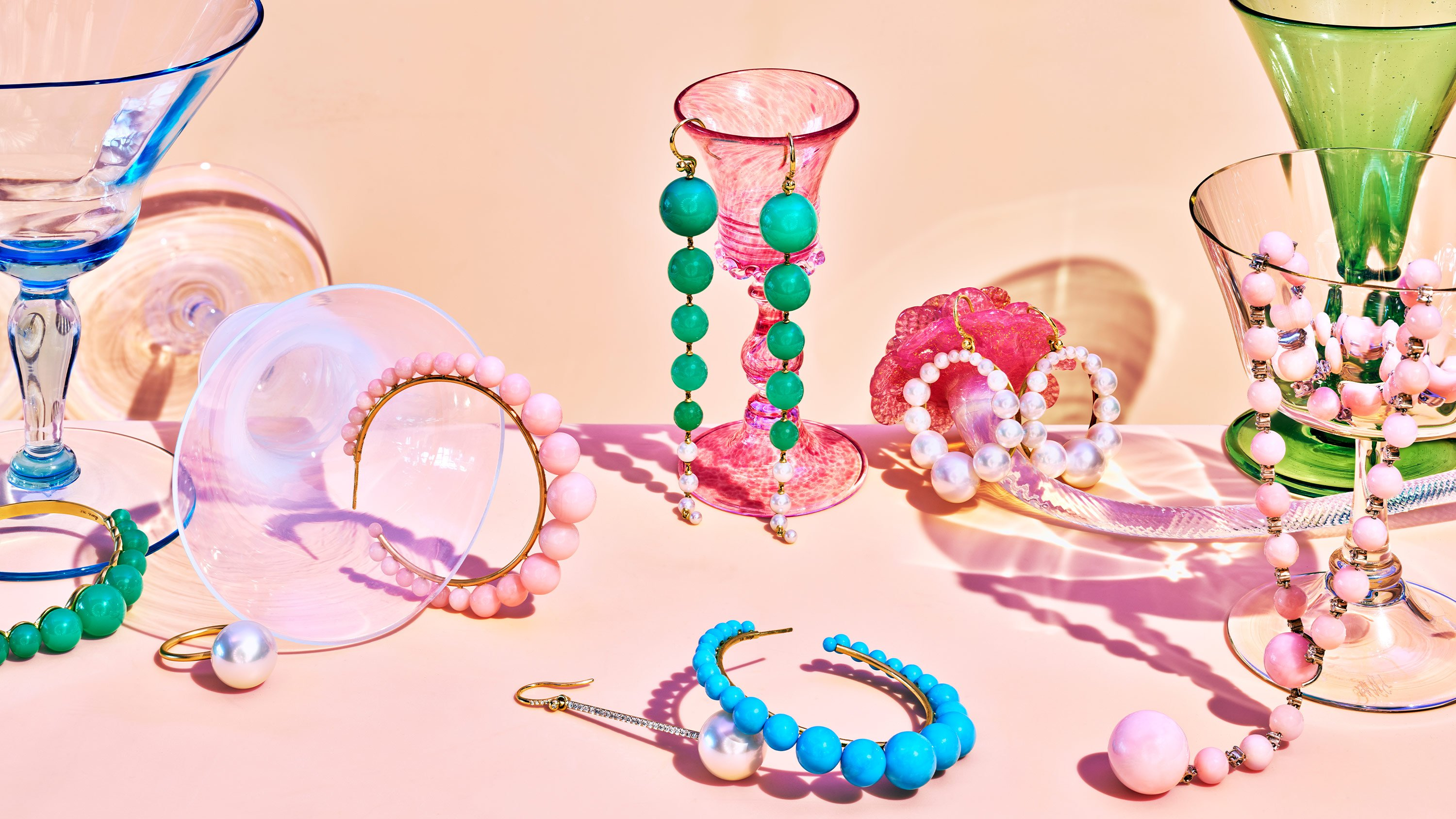 Irene Neuwirth gumball collection spread. Rings, necklaces, headpieces and earrings displayed on colored glasses. Art direction by RoAndCo