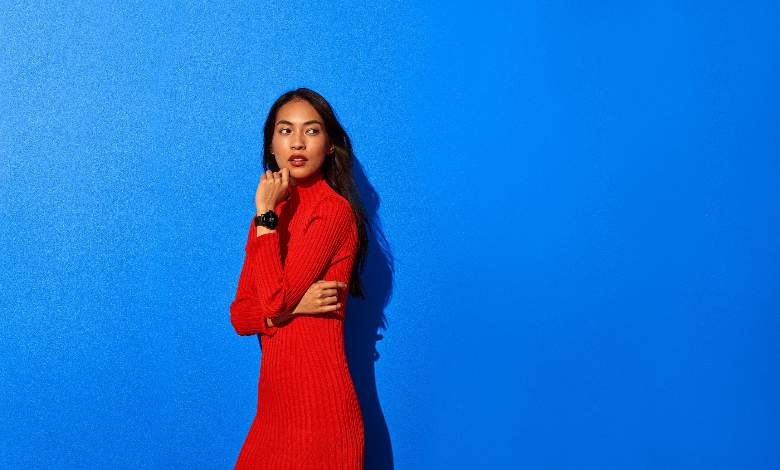 Woman in all red standing in front of blue background, wearing black Google Wear OS watch. Campaign art direction by RoAndCo Studio