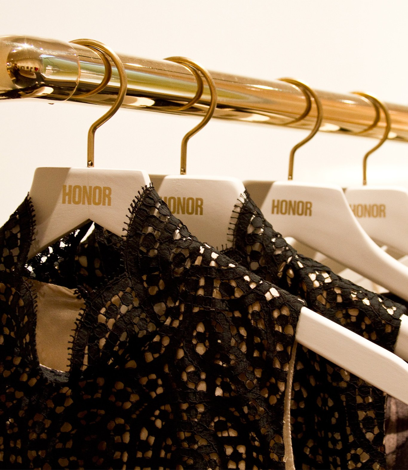 Close-up of clothing rack with custom Honor hangers, design by RoAndCo Studio