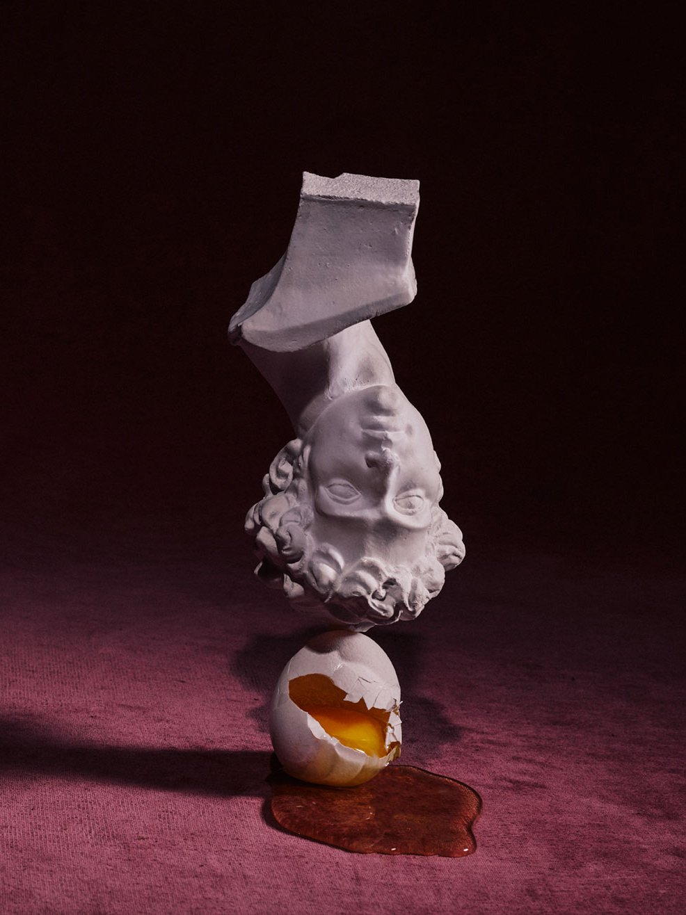 Still life image of upside down bust balancing on top of a broken egg. Romance Journal Issue 02 Resistance. Publication design, art direction, print design by RoAndCo.