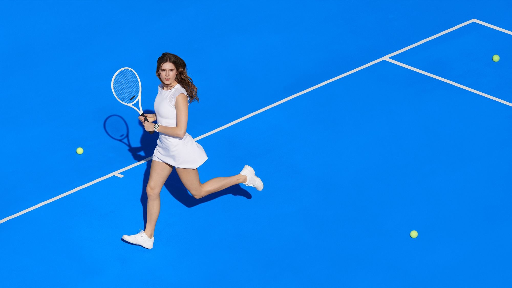 Woman playing tennis wearing a white dress and Google Wear OS watch, art direction by RoAndCo