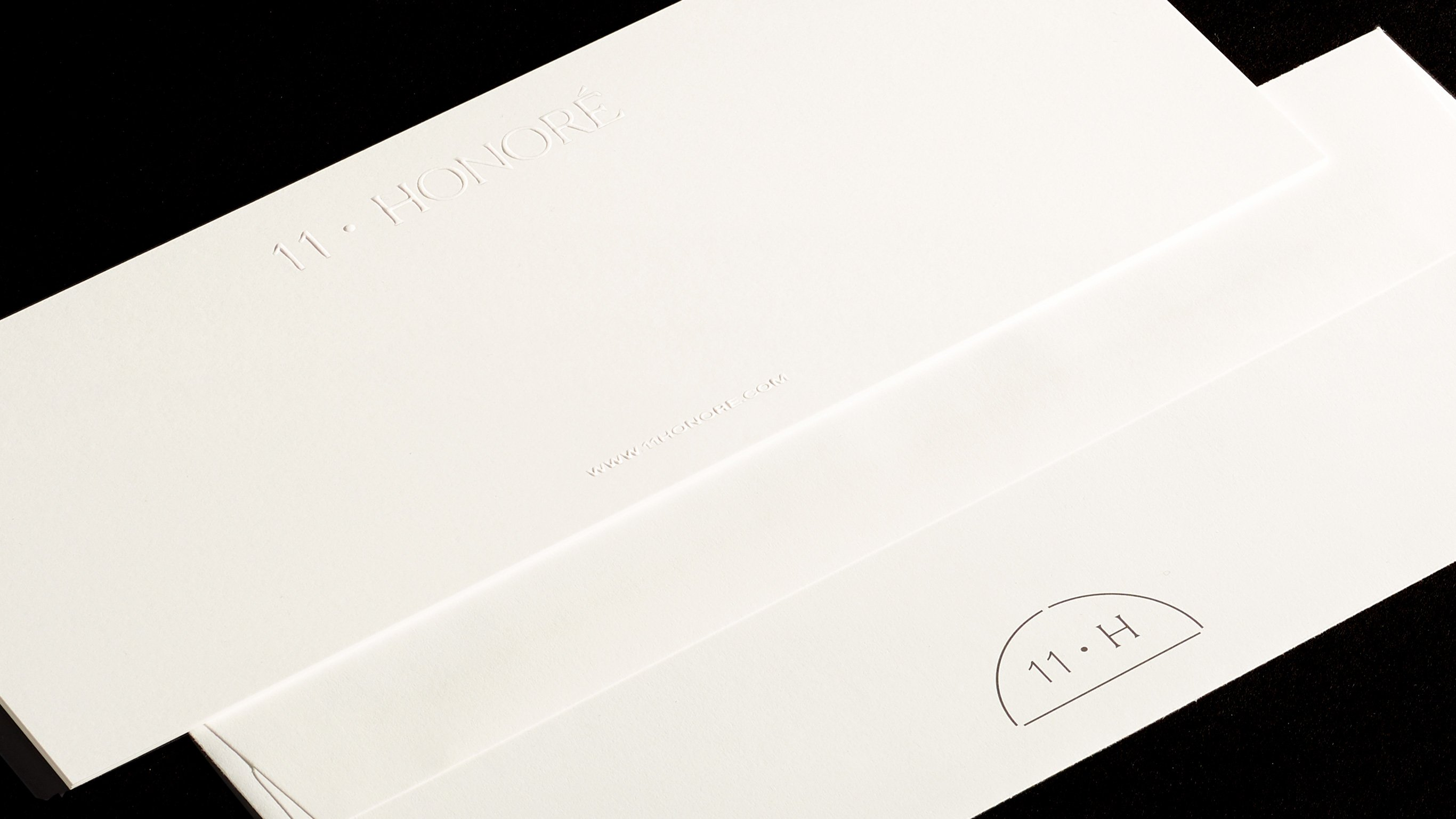 Close up of 11 Honoré embossed envelopes with 11 H seal, print design and branding by RoAndCo