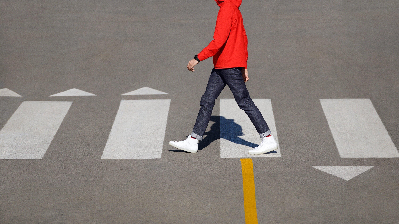 Man crossing the street, wearing black Google Wear OS watch. Art Direction by RoAndCo Studio