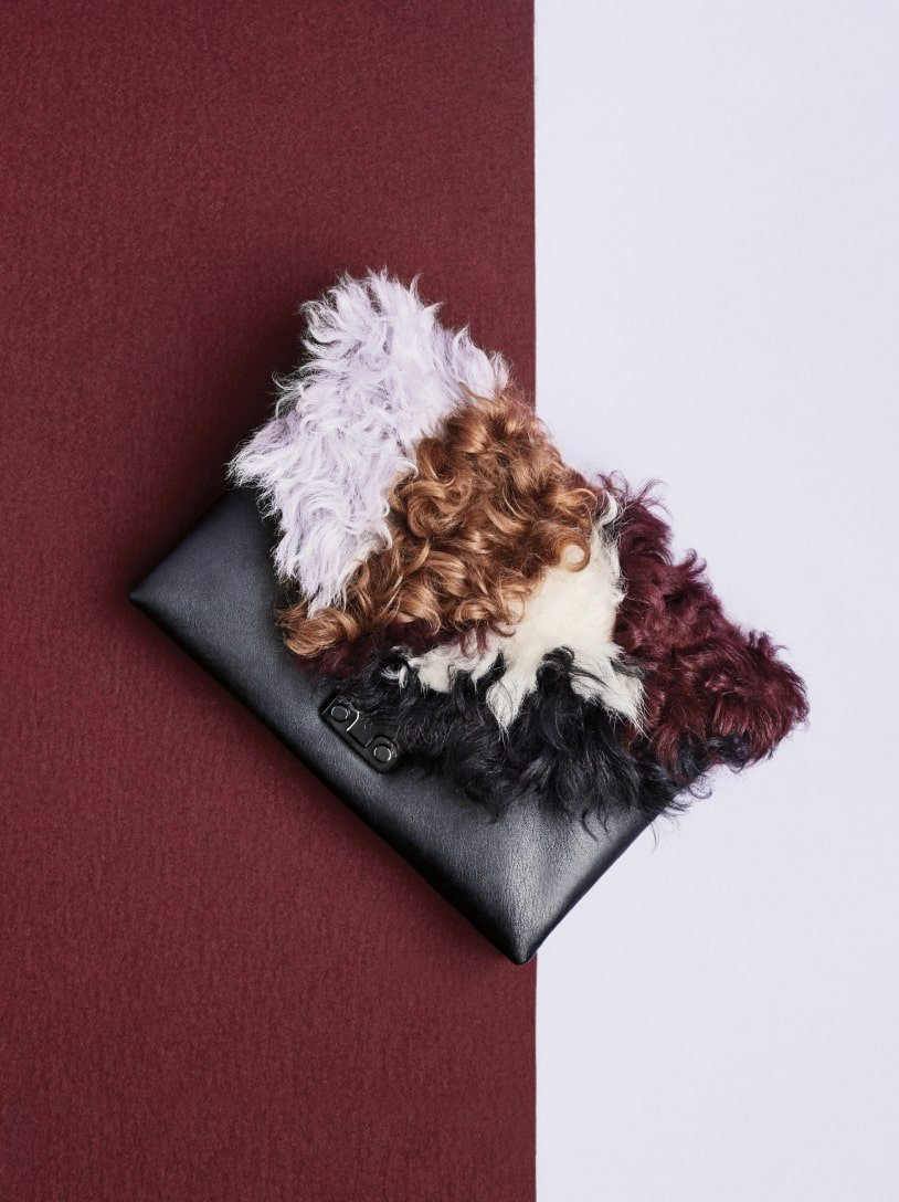 Close up of black leather Loeffler Randall pouch with multi-color faux-fur accents. Art direction by RoAndCo
