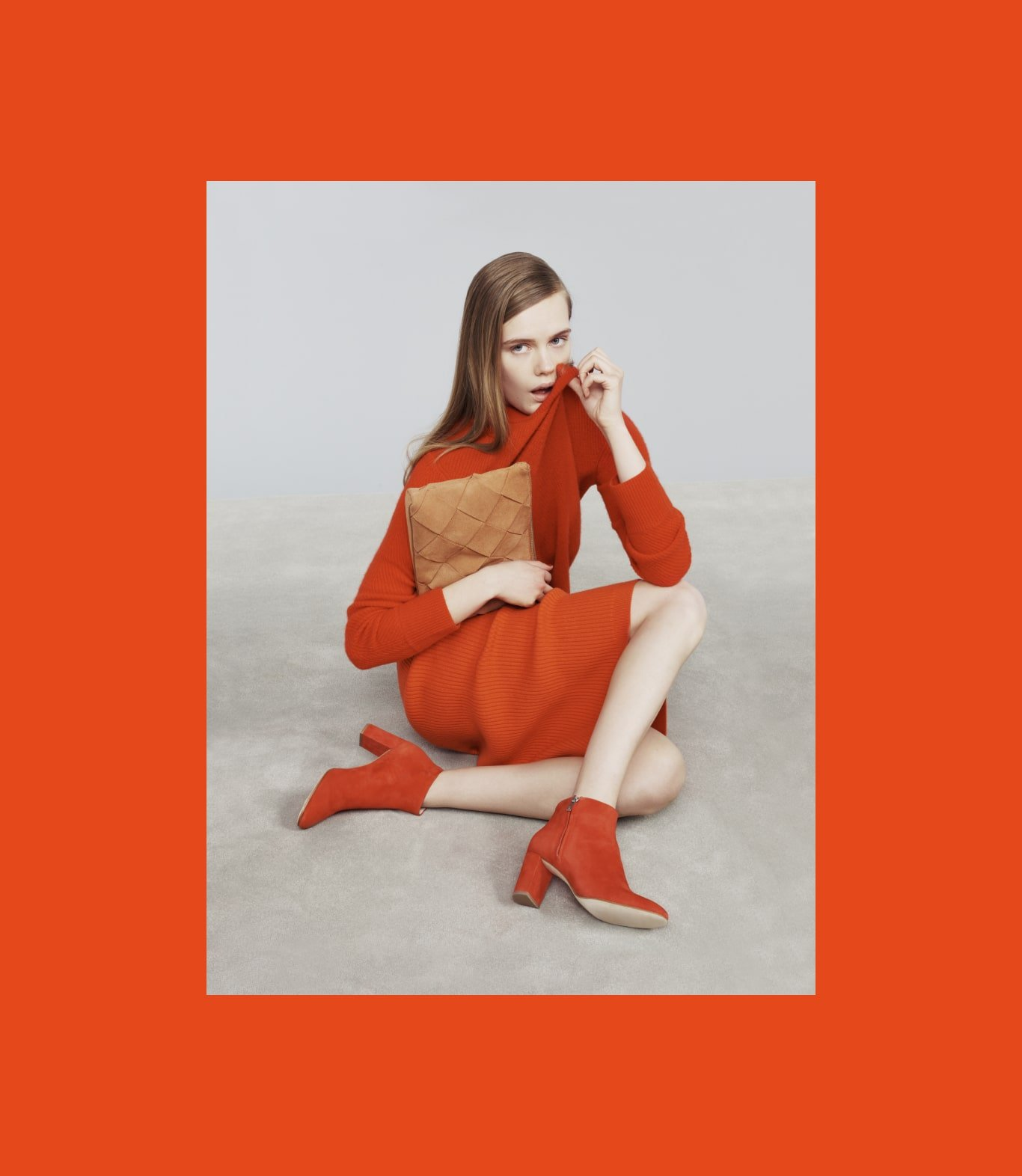 Model wearing red turtleneck dress and red Loeffler Randall boots. Art direction by RoAndCo