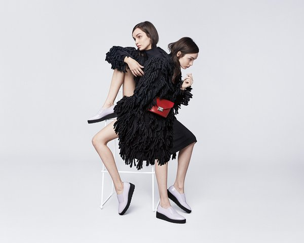 Two models leaning on a stool. Purple Loeffler Randall loafers and red envelope purse. Art Direction by RoAndCo