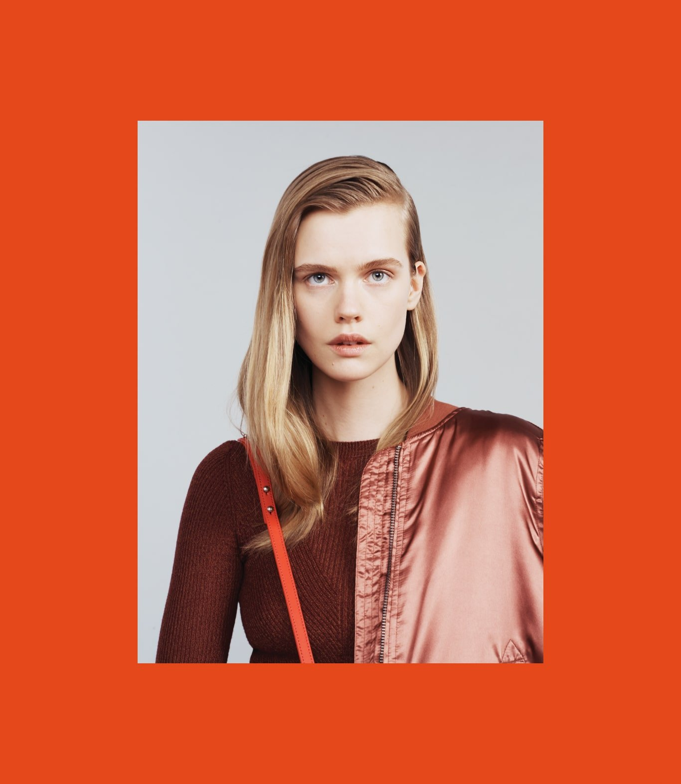 Blonde model wearing red bomber jacket and red Loeffler Randall cross-body purse. Art direction by RoAndCo