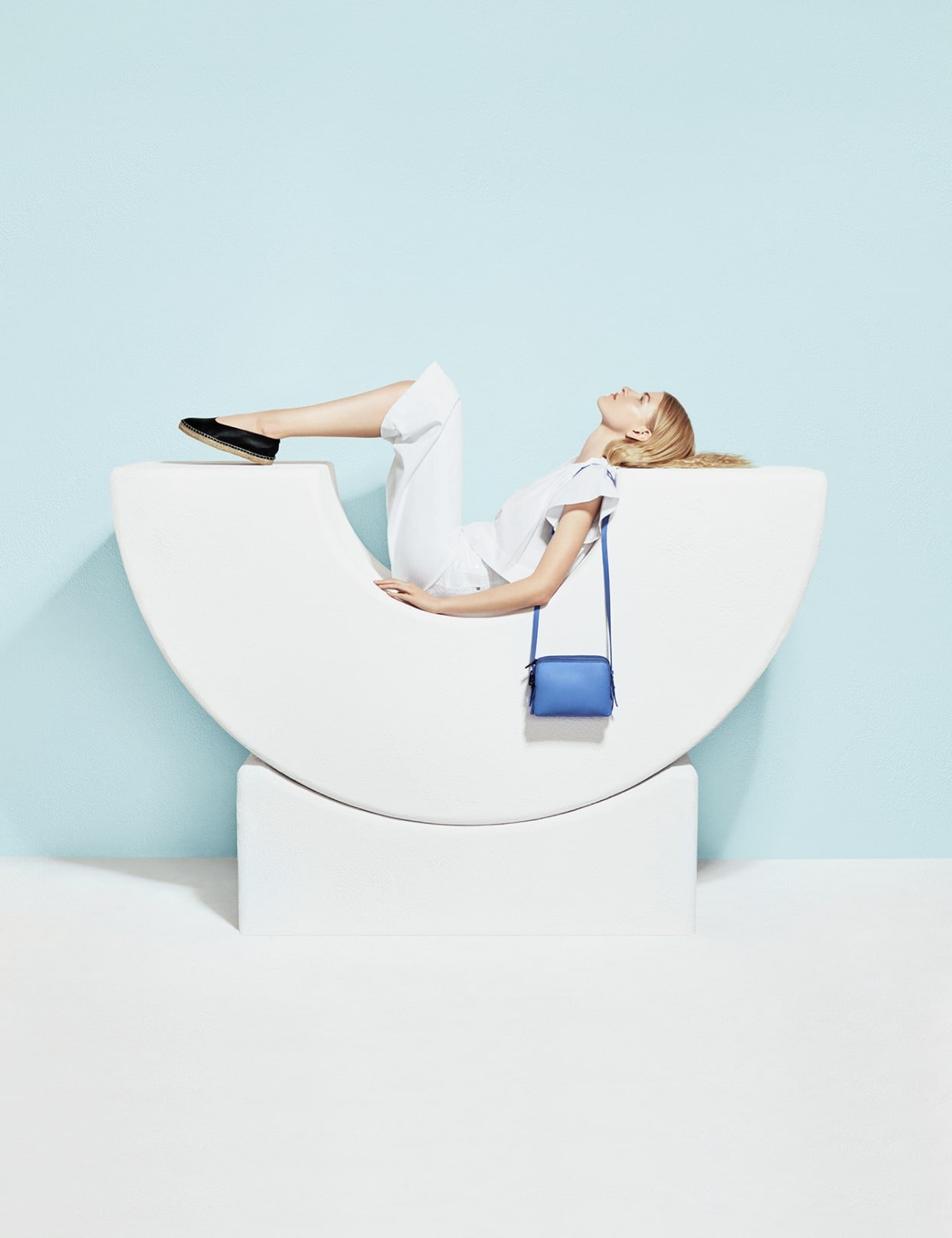 Model sitting in white arch with light blue Loeffler Randall cross-body purse. Art direction by RoAndCo