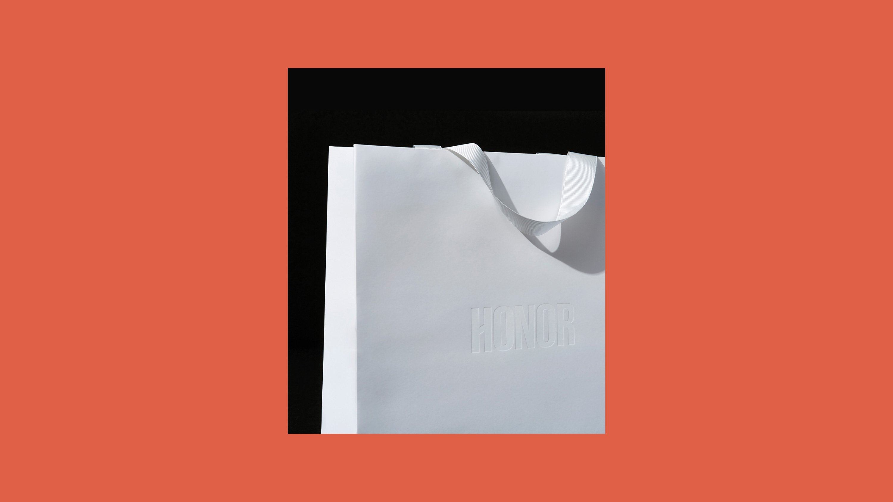 White Honor shopping bag with embossed logo, print design by RoAndCo Studio