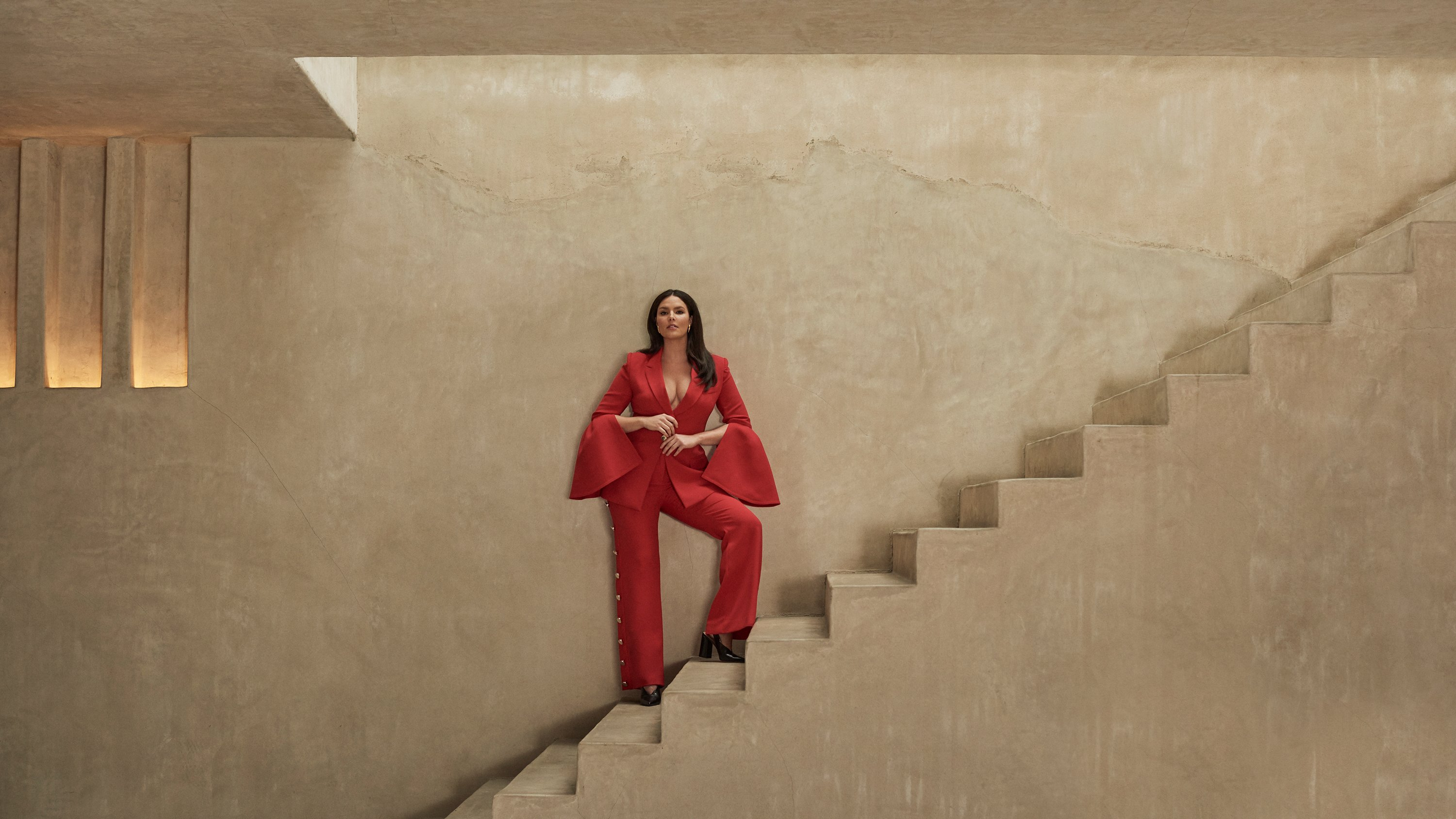 Model Candice Huffline wearing red power suit with dramatic sleeves, Ad campaign. Art Direction by RoAndCo